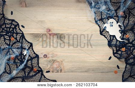 Halloween background. Spider web, black cobweb lace and scary ghosts decorations as the symbols of Halloween holiday on the wooden background