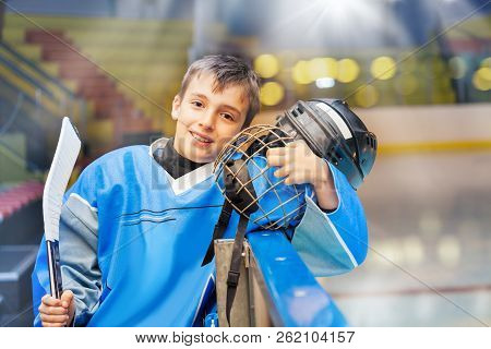 Young Hockey Player Standing Next To Rink Boards