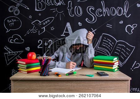 Apathetic and uninterested youngster sitting at the desk with a head leaned on the fists, surrounded with school supplies. Chalkboard as a background poster