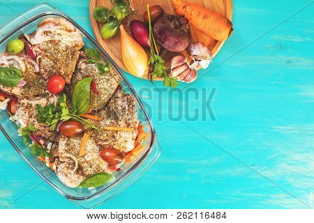 Raw Fresh Chicken Thighs With Spices And Vegetables In A Glass Bowl