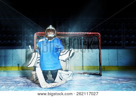 Young Goaltender Guards His Net During Hockey Game