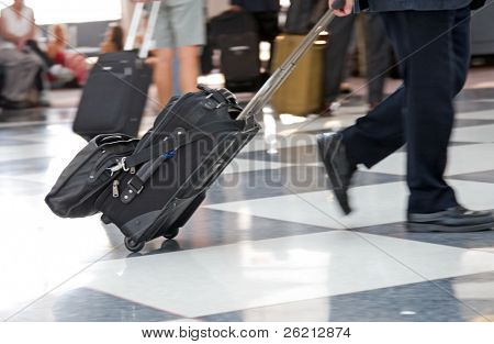 Airline travelers and passengers rush through the terminal to their flights with their baggage and luggage