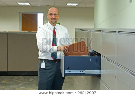 A man in his corporate office environment, on the phone and at work