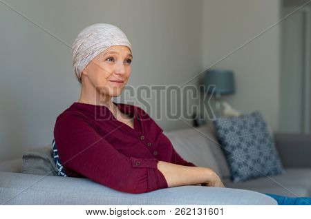 Portrait of mature woman recovering after chemotherapy. Senior woman fighting breast cancer and wearing a headscarf. Hopeful ill lady at home looking away while sitting on sofa.