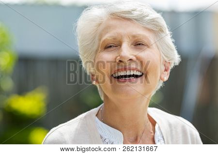 Portrait of a beautiful senior woman laughing outdoor. Mature woman with grey hair enjoying and smiling. Cheerful older woman relaxing in outdoor garden.