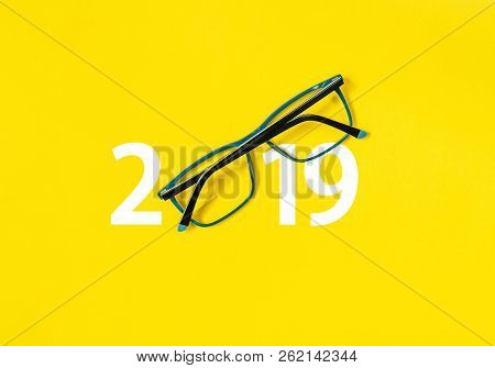 Happy New Year 2019. 2019 With Glasses On Yellow Isolated Background