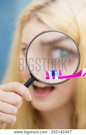 Beautiful Perfectionist Young Woman Checking Her Tooth Brush Through Manifying Loupe Glass. Hygiene,
