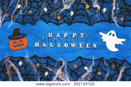 Halloween background. Happy Halloween letters and Halloween decorations on the dark blue wooden background, Happy Halloween concept