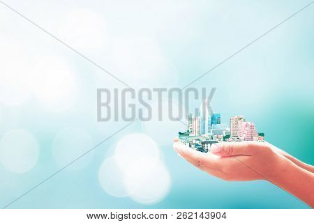 Sustainable Development Concept: Human Hands Holding Hotel In Big City On Blurred Nature Background