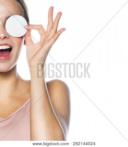 closeup portrait of attractive young caucasian smiling woman brunette isolated on white studio shot lips toothy smile face head and shoulders clean?ng her face w?th cotton d?sks