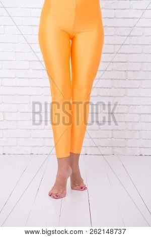 Sport Wear Fashion. Orange. Practicing In Ballet Studio. Woman In Orange Leggings On Legs. Dancing B