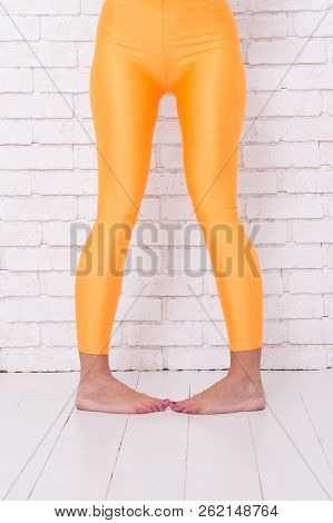 Playful Girl In Crazy Dancing Ballet Position Of Feet. Woman In Orange Leggings On Legs. Dance To Rh