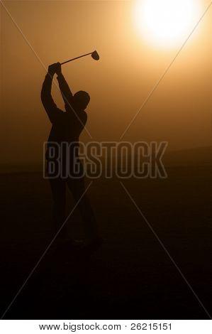 Lone golfer stands in golden morning sunlight
