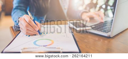 Woman Hand Writing On Charts And Graphs That Show Results With A Pen And Using A Laptop Computer Wor