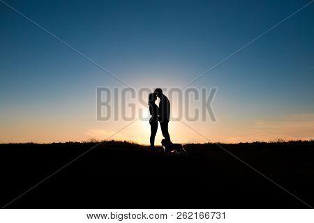 Romantic Couple Hug At Sunset On Background.
