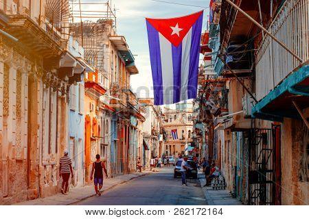 HAVANA,CUBA - SEPTEMBER 29,2018 : Urban scene with cuban flags, people and aged buildings in Old Havana