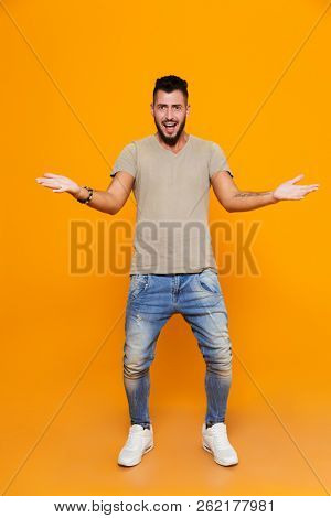 Full length portrait of a confused young casual man standing isolated over orange background, shrugging shoulders