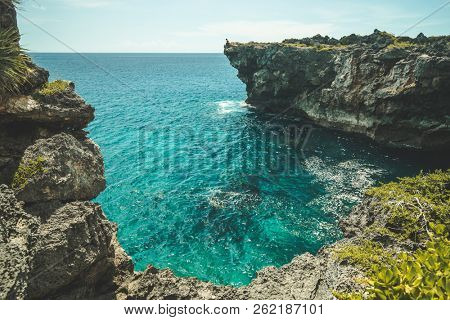 Close-up turquoise bay, vertical cliffs. Indonesia, Sumba island. Spectacular scenery the cozy bay with transparent blue water surrounded by the green-capped cliffs. Indian ocean.