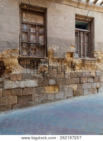 Angled View Of Two Adjacent Broken Windows And Grunge Stone Bricks Wall In Abandoned Darb El Labana