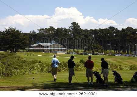 Golfers waiting in the shade to tee off, heading for the clubhouse