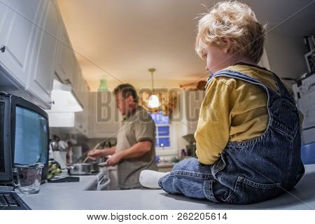 Toddler boy sitting on kitchen counter watching tv while father