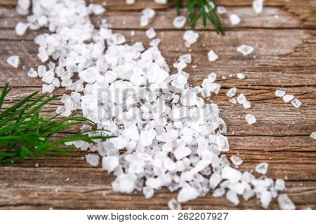 Crystals Of Large Sea Salt And Dill On A Wooden Table. Background For Advertising Salt. Table Salty.