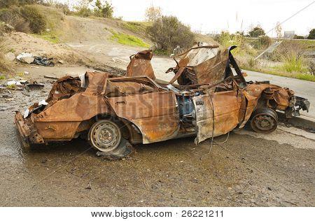 Burnt wreck of a car in a cul de sac