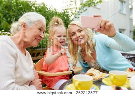 family, generation and people concept - happy mother, daughter and grandmother taking selfie by smartphone at cafe or restaurant terrace