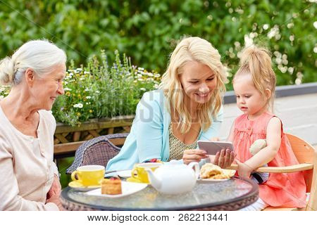 family, generation and technology concept - happy mother, daughter and grandmother using smartphone at cafe or restaurant terrace