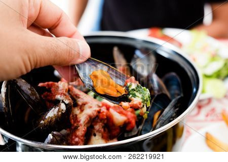 closeup of a man eating some moules a la bonifacienne, a recipe of mussels typical of Bonifacio, in Corsica, France