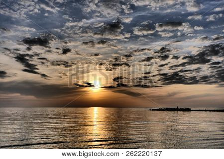 Evening Atmosphere - An Impressionistic Sunset On The Baltic Sea Coast With Calm Sea And Many Small