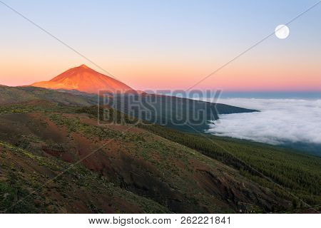 The Peak Of El Teide Above The Clouds With Full Moon During Sunrise.