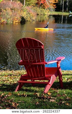 Red wooden chair with kayaker during autumn season