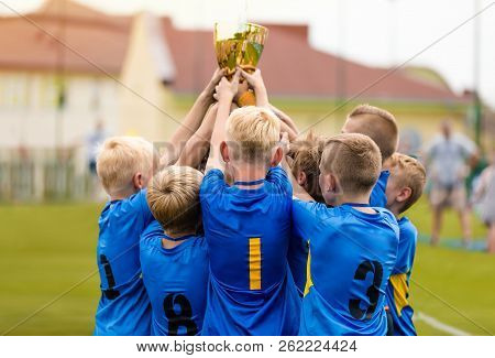 Young Soccer Players Holding Trophy. Boys Celebrating Soccer Football Championship. Winning Team Of