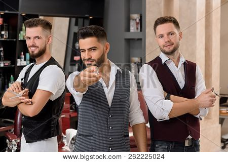 Three handsome hairstylists posing and standing in barbershop. Charming bearded master pointing with scissors at camera and winking. Masters looking at camera and holding instruments for hairstyling. poster