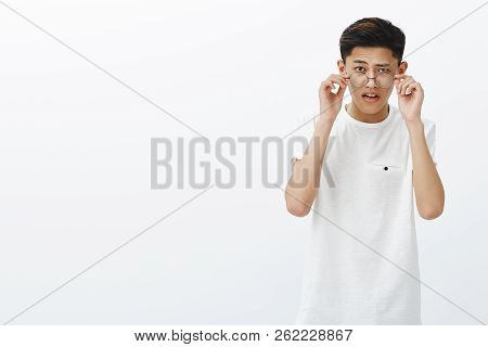 Asian Guy Taking Off Glasses As Being Doubtful Seeing Strange Thing Looking Amazed And Surprised Ope