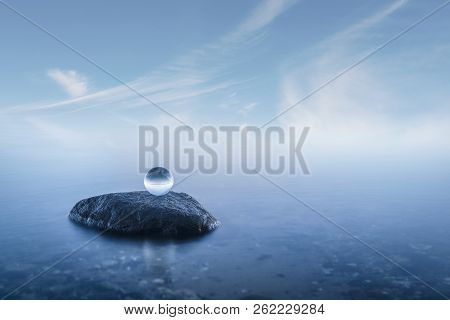 Crystal Ball On A Rock In A Misty Seascape With Calm Blue Waters
