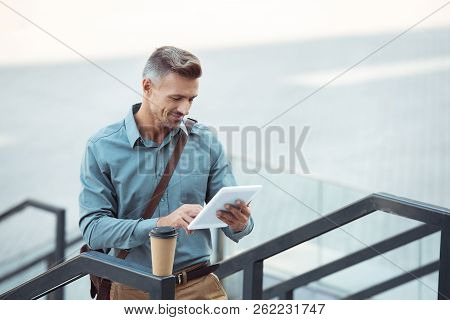 Handsome Smiling Middle Aged Man Using Digital Tablet On Stairs