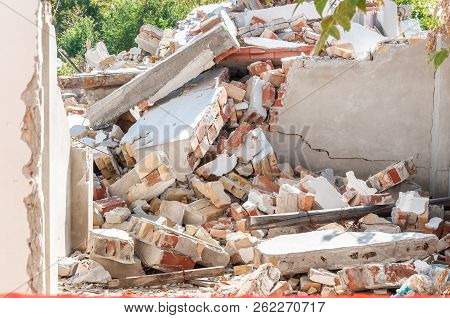 Remains Of Hurricane Or Earthquake Disaster Damage On Ruined Old House With Collapsed Roof And Walls