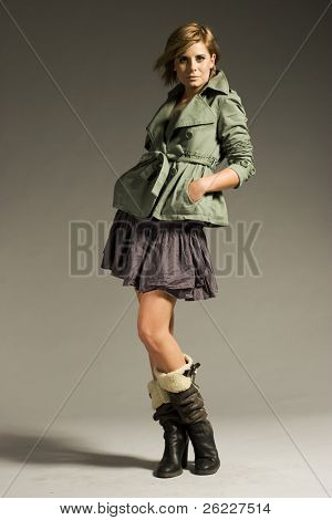 beautiful blonde girl wearing green coat and mini skirt on grey background