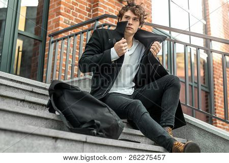 Pensive Man Sitting On Concrete Steps And Wrapping Up In Black Coat