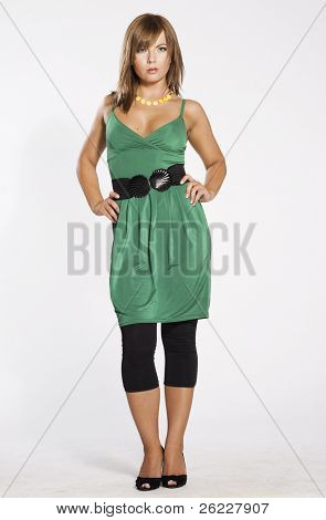 attractive and sexy blonde woman wearing green dress on light background