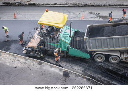 Asphalt Paver Machine Places A Layer Of New Asphalt. Dumper Unloads Asphalt. A Cold Autumn Day. Road