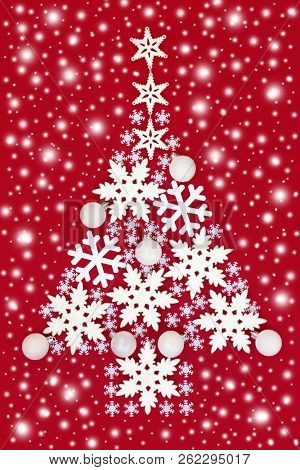 Abstract Christmas tree with white snowflake and round bauble decorations with snow on red background. Traditional Christmas greeting card for the holiday season.