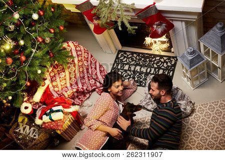 Christmas couple at home in Winter. Happy young couple lying on floor at home with dog at Christmas time. Christmas tree and fireplace in background.