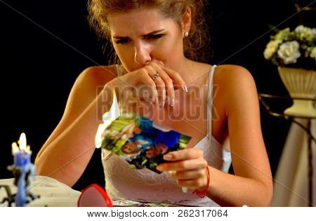 Wedding bride sitting night table. Quarrel during honeymoon. Boyfriend left girlfriend. Couple break up. Leaved woman burns photos of ex-boyfriend.