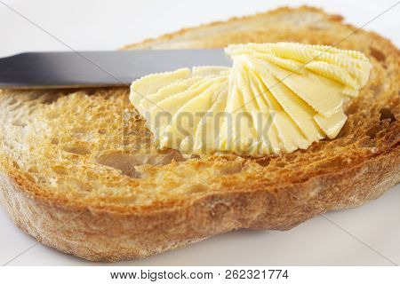 Soft, Heart Healthy, Polyunstaurated Margarine Being Spread Onto Crunchy Toast.