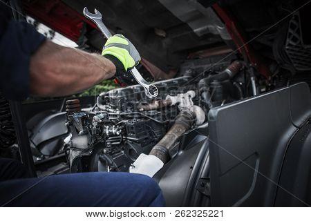 Caucasian Truck Mechanic Repairing Semi Truck Engine.