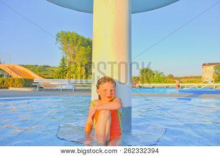 Little Girl Sitting Under A Sprinkler, Shower In Swimming Pool. Portrait Of Little Cute Girl In The