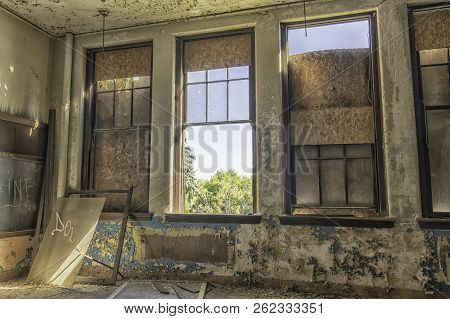 An Schoolroom In An Abandoned Detroit School. The Windows Are Broken And Partially Boarded Up.